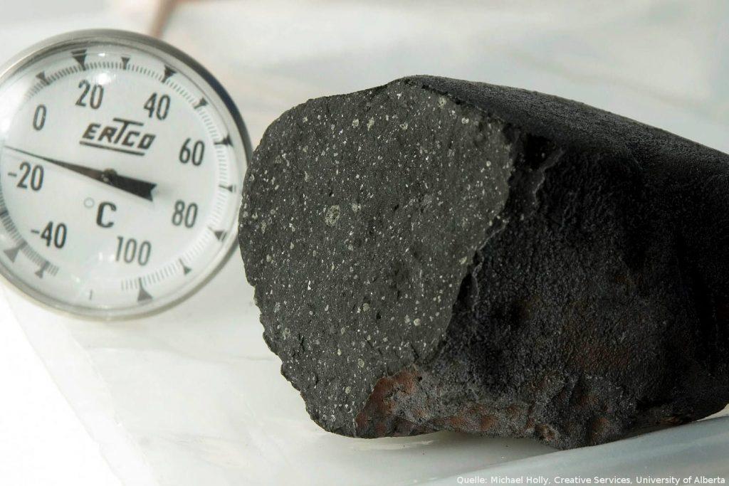 Meteorit vom Tagish-See: Auf den mit Leuchtdioden bestrahlten Nachtaufnahmen dieser etwas krumpeligen Oberflächen entdeckten die Forscher in der fast schwarzen Gesteinsmatrix helle Einsprengsel von Mineralen, die an Mineralinklusionen in Meteoriten vom Tagish-See erinnern.
