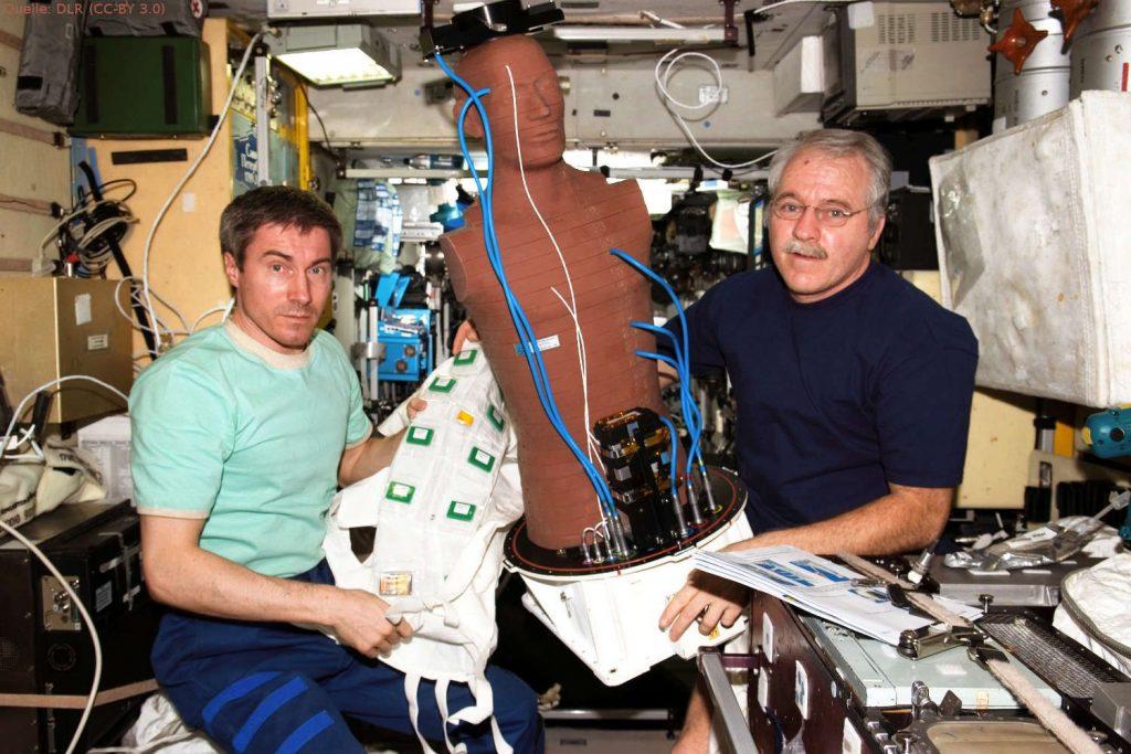 MATROSHKA misst die Weltraumstrahlung: Die Astronauten Sergey Krikalev (l.) und John Phillips mit der Spezialpuppe MATROSHKA zur Messung der Weltraumstrahlung. Das Foto wurde auf der ISS aufgenommen.
