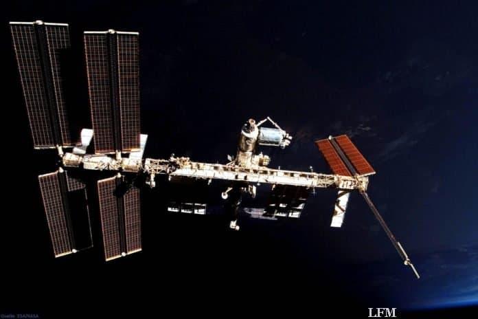 ISS und Columbus-Labor vor der unbeleuchteten Erde: Die Internationale Raumstation ISS schwebt über der Nachtseite. In blau erscheint am rechten Bildrand der beleuchtete Teil der Erde. In der Bildmitte ist das europäische Columbus-Labor, als hell glänzende Tonne zu erkennen, das im Februar 2008 an der ISS montiert wurde.