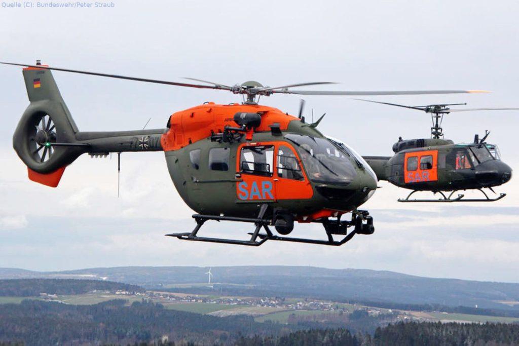 Airbus H145 LUH SAR (vorne) und Rettungshubschrauber Bell UH 1D fliegen nebeneinander über Holzdorf.